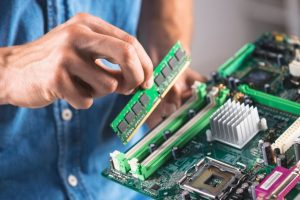 close-up-engineer-putting-ram-memory-module-computer-motherboard_23-2147883863